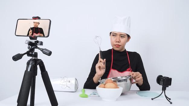 Food blogger live streamen. online-kochlehrerin. kochen mit abonnenten über die telefonkamera online.