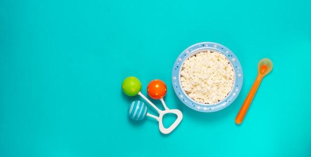 Food bowl mit hüttenkäse, babynahrung, rassel und löffel, auf blauem hintergrund, draufsicht, horizontal. ,