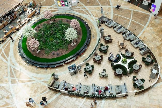 Food court mit sitzenden leuten im einkaufszentrum. ruhen und meetings abhalten. ansicht von oben. moskau, russland, 21.07.2021.
