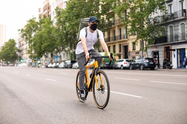 Food delivery bike mit coronavirus-maske mit rucksack und taschen
