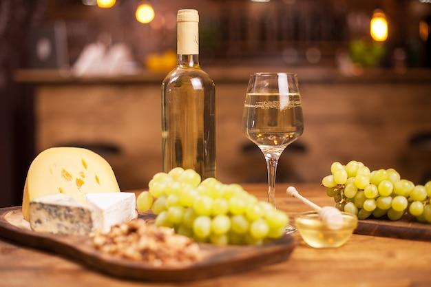 Food-festival mit verschiedenen käsesorten und weißwein in einem vintage-restaurant. flasche weißwein. frische trauben.