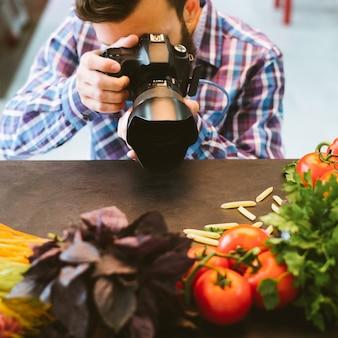 Food-fotografie. vegetarischer lifestyle-blog. männlicher stylist, der ein foto von bio-zutaten macht.