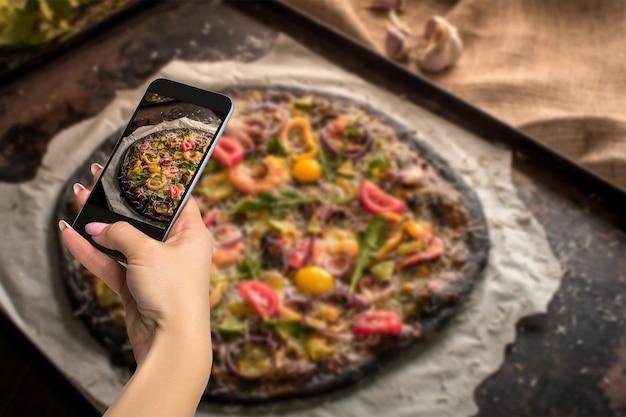 Food-konzept fotografieren - frau fotografiert italienische pizza mit schwarzem teig und meeresfrüchten auf einem backblech aus dem ofen. fotografieren mit einem handy oder tablet