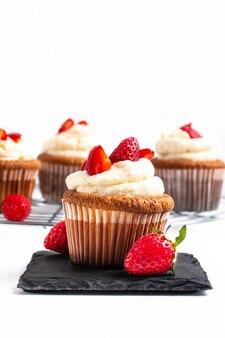 Food-konzept frische hausgemachte erdbeeren schlagsahne cupcake auf weißem backfround