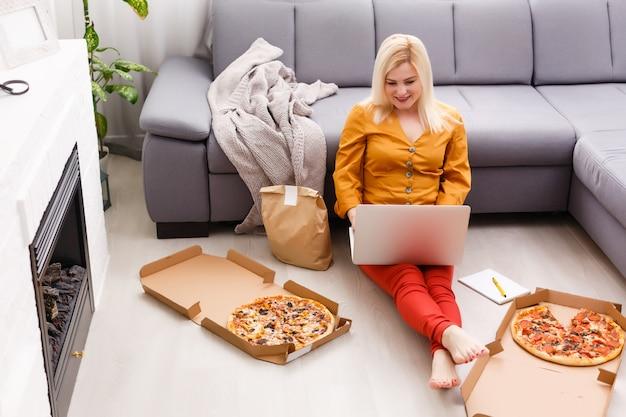 Food order konzept. nahaufnahme draufsicht einer bestellenden pizza mit einem laptop.