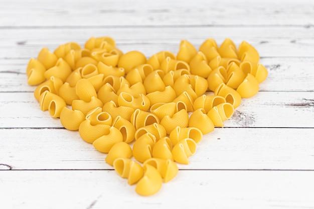 Food.pasta rohe nahaufnahme hintergrund. köstliche trockene ungekochte zutat für traditionelle italienische küche. strukturierte vielfalt formen. ansicht von oben. herzform.