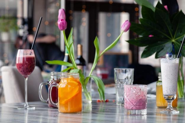 Food-stylist und fotograf dekorieren und bereiten verschiedene cocktails, milchshakes und smoothies vor.