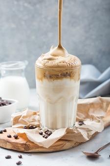 Food trend - dalalgona kaffee, geschlagenes instantgetränk auf rustikalem hintergrund