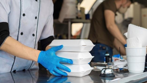 Foodtruck, koch hält drei fertige bestellungen