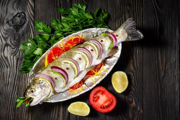 Forelle des rohen fisches kochte für das kochen mit zitrone und tomaten auf einer platte mit folie.