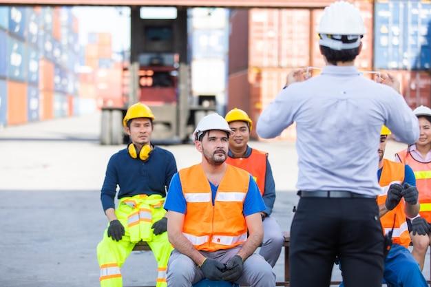 Foreman bringt arbeitern bei, wie man gesichtsmasken trägt und auf sich selbst aufpasst, während sich das coronavirus verbreitet.