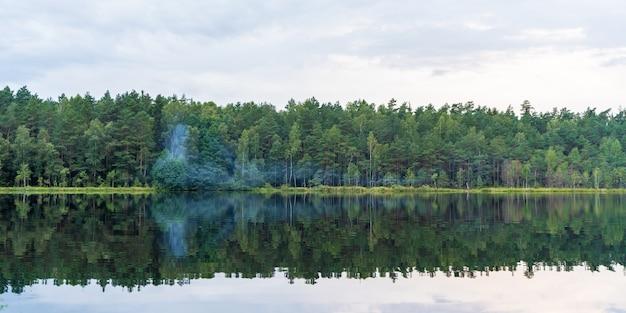 Forest lake am sommertag, landschaftsfoto mit rauch auf dem wasser. bäume, rauch und himmel, die sich im see widerspiegeln.
