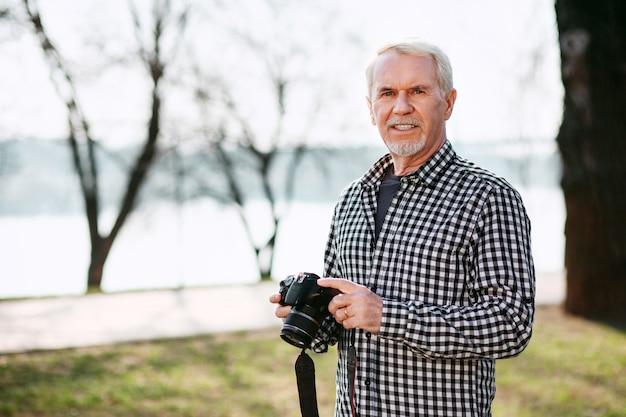 Form der kameraausrüstung. ansprechender älterer mann, der im freien aufwirft und kamera verwendet