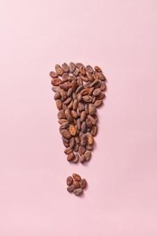 Form des ausrufezeichens aus natürlichen organischen trockenen kakaobohnen auf hellrosa hintergrund mit kopierraum. wirkung der verbesserten menschlichen gehirnaktivität durch schokolade.