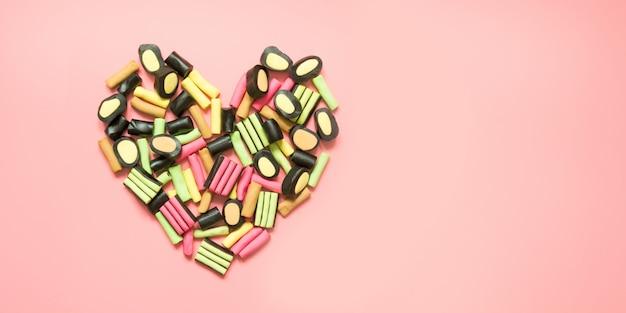 Form des herzens. bunte lutscher- und süßholzsüßigkeit auf rosa.