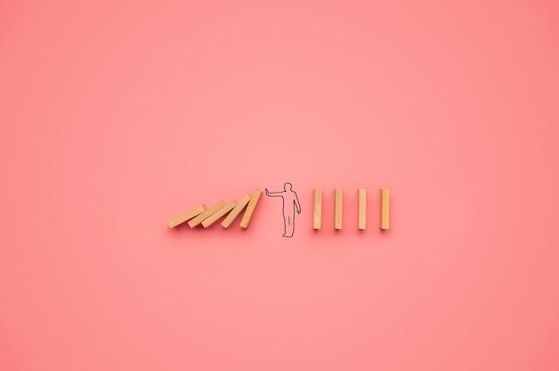 Form eines mannes, der verhindert, dass dominosteine in ein konzeptuelles bild fallen. über rosa hintergrund.