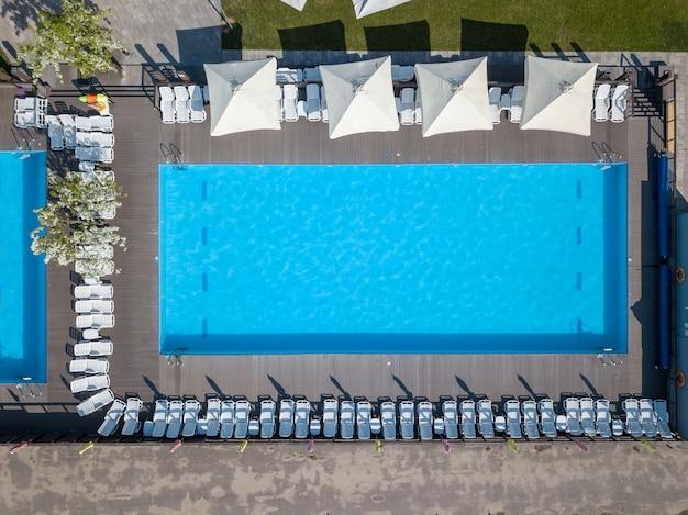 Form und kurven des großen blauen schwimmbades mit betten und sonnenschirmen auf dem grünen garten. urlaubskonzept. foto von der drohne