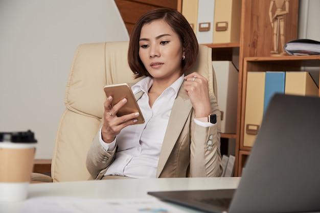 Formale geschäftsfrau, die telefon im büro verwendet