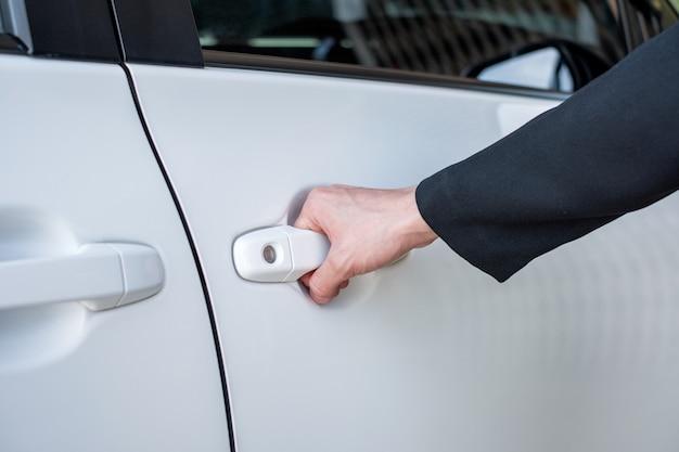 Formale hand auf dem griff, der eine autotür öffnet