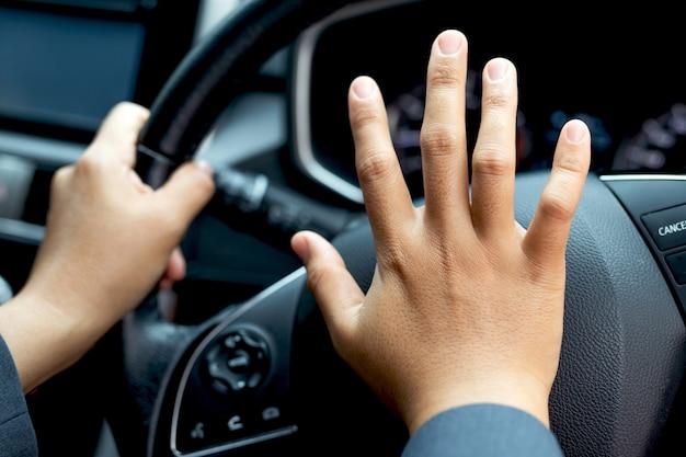 Formell gekleidete frau hupt beim autofahren