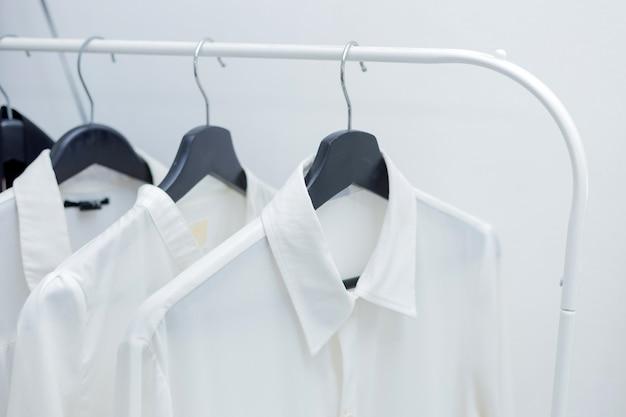 Formelle hemden hängen an einem kleiderbügel