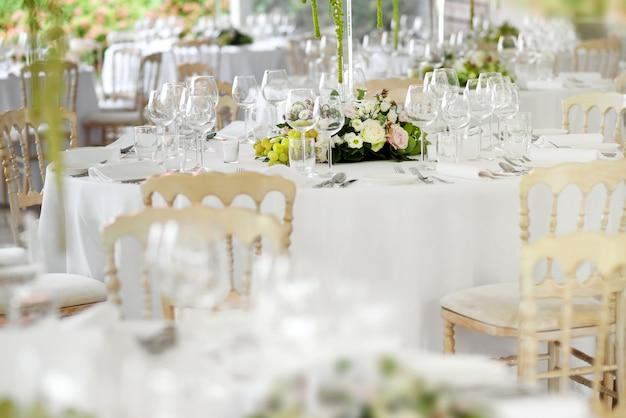 Formelle tischdekoration an einem hochzeitsort mit stilvollen weißen stühlen, elegantem glas und besteck um florale mittelstücke mit selektivem fokus auf einen tisch