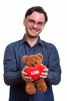 Formeller junger glücklicher mann, der lächelt, während er teddybär hält
