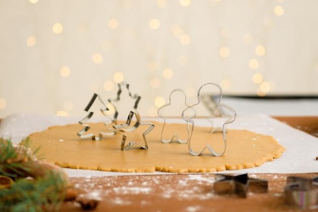 Formen für lebkuchenweihnachtsmänner und -sterne, nahaufnahme, draufsicht, roher teig mit zimt zum backen vorbereitet.