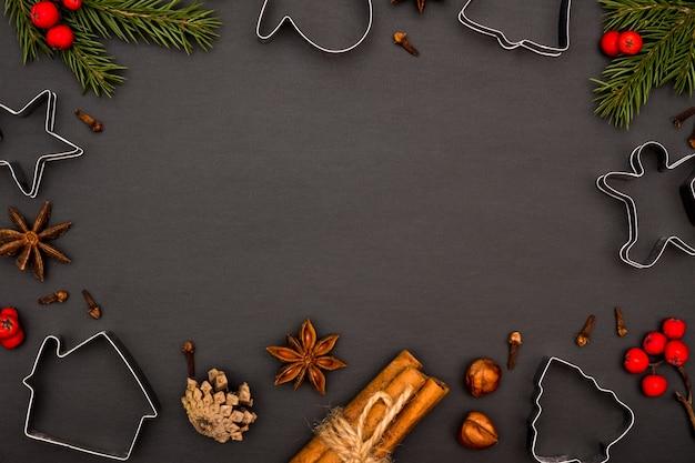Formen und gewürze für die herstellung von weihnachtsplätzchen auf einem schwarzen hintergrund