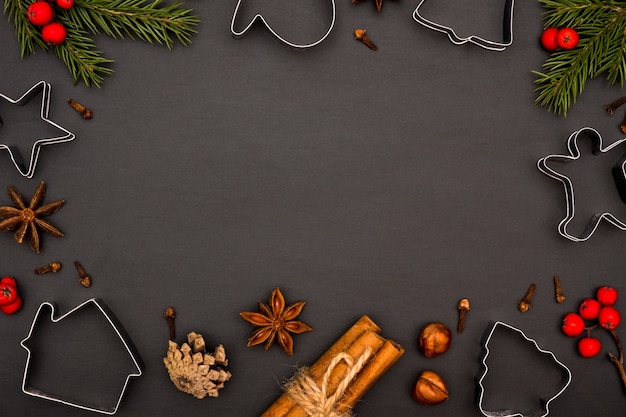 Formen und zutaten für die herstellung von weihnachtsplätzchen auf einem schwarzen hintergrund