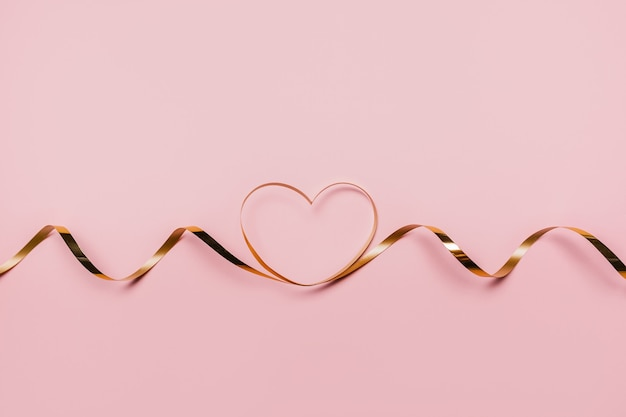 Formherz durch goldband auf lokalisiertem rosa hintergrund