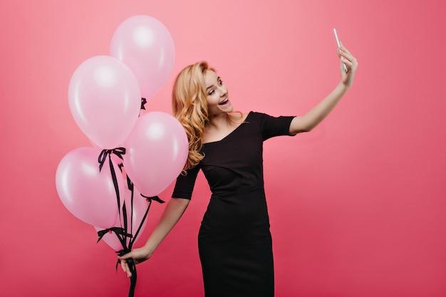 Formschön faszinierende junge frau, die neues telefon für selfie verwendet. lachendes geburtstagskind, das foto von sich selbst macht, während es großen haufen partyballons hält.