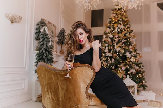 Formschöne braunhaarige frau, die auf sessel mit weinglas vor weihnachtsbaum entspannt. elegante kaukasische dame im schwarzen kleid, die freunde auf neujahrsparty wartet.