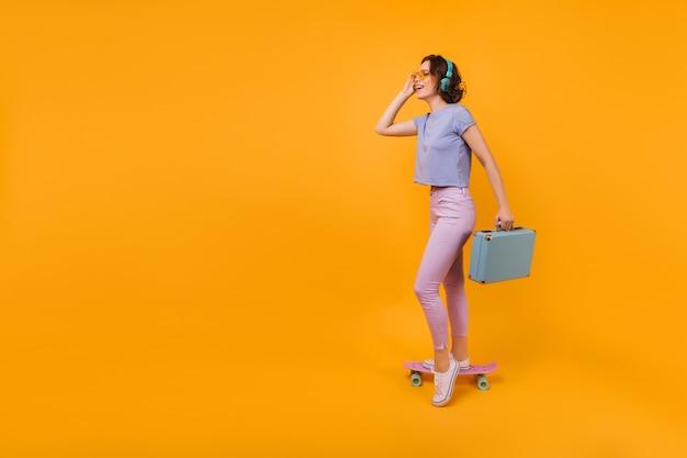 Formschöne dame in weißen gummischuhen, die mit blauem koffer aufwirft. foto der gut gelaunten kurzhaarigen frau, die auf longboard steht.