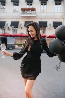 Formschöne frau im modischen schwarzen kleid, die auf stadtplatz tanzt und luftballons winkt