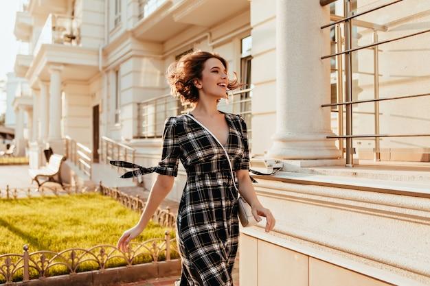 Formschöne frau in elegantem kariertem kleid, die die straße entlang geht und lacht. schönes weißes weibliches modell mit kurzem haarschnitt, der zeit im freien verbringt.