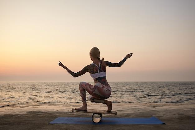 Formschöne junge tätowierte dame mit blondem haar hält gleichgewicht mit erhobenen händen, balanciert auf holzbrett während des sonnenaufgangs, trägt sportliche kleidung