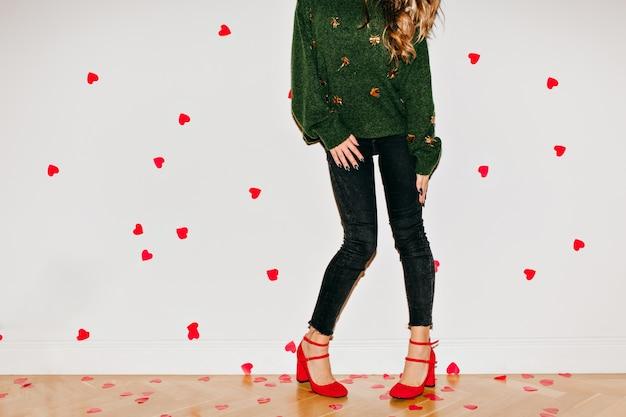 Formschöne, lockere frau im grünen pullover, die auf der etage tanzt