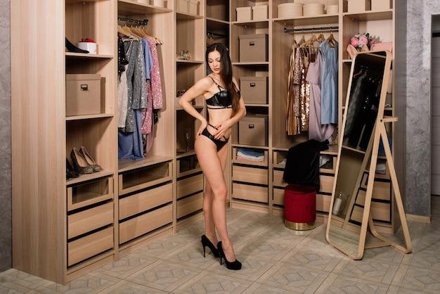 Formschöne verführerische frau in weiß-schwarzen dessous, die in der garderobe, in der nähe des kleiderschranks, des badezimmers steht