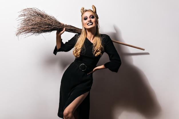 Formschöner weiblicher vampir, der mit schwarzem make-up aufwirft. attraktive hexe mit besenkühlung auf halloween-party.