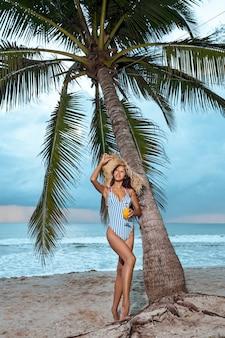 Formschönes asiatisches mädchen mit der glänzenden haut, die am exotischen erholungsort nach dem sonnenbad aufwirft. sinnliche brunettefrau im modischen bikini, der nahe palme steht. sommerurlaub