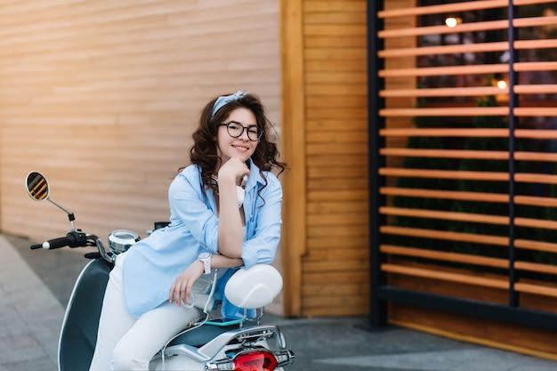 Formschönes dunkelhaariges mädchen mit verspieltem lächeln, das auf moped aufwirft und mit interesse schaut