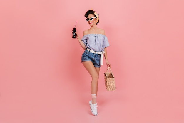 Formschönes pinup-mädchen, das eine flasche soda hält und lächelt. atemberaubende europäische frau mit sommertasche, die auf rosa hintergrund aufwirft.