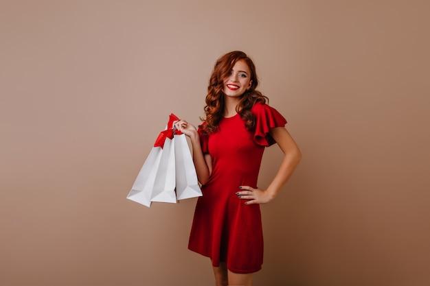 Formschönes rothaariges mädchen, das nach dem einkaufen aufwirft. weiblicher shopaholic trägt rotes kleid.