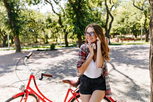 Formschönes süßes mädchen, das mit fahrrad im park aufwirft. glückliche europäische dame, die sommermorgen im freien verbringt.