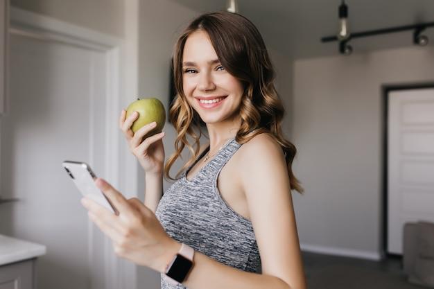 Formschönes süßes mädchen, das mit grünem apfel zu hause aufwirft. innenfoto der glückseligen lockigen frau, die smartphone mit lächeln hält.