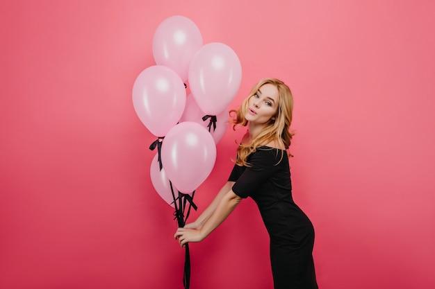 Formschönes süßes mädchen mit weißer haut lustig posiert mit heliumballons. innenporträt des überraschten lockigen weiblichen modells, das auf der party tanzt.
