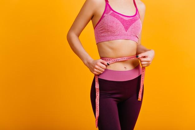 Formschönes weibliches modell, das versucht, gewicht zu verlieren