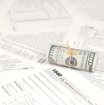 Formular zur einkommenssteuererklärung mit dollarbanknotenrolle