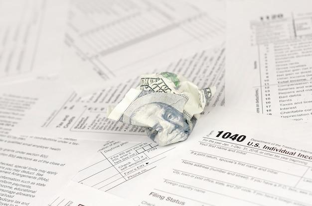 Formular zur einkommenssteuererklärung und zerknitterter hundert-dollar-schein